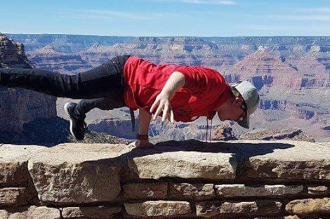 Photo of Josh balancing on one arm on a wall overlooking the Grand Canyon. Paedriatric Rheumatology Network.