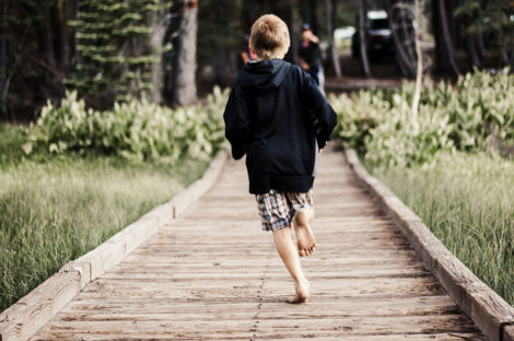 Photo of boy running along a jetty. Paediatric Rheumatology Network supports kids with Juvenile dermatomyositis and other conditions.